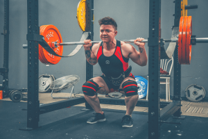 man with a lot of muscles doing squat inside a squat rack