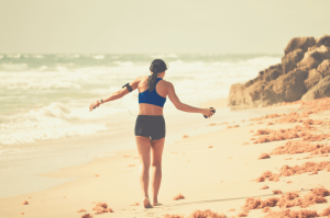 a woman walking down the beach holding heart rate monitor
