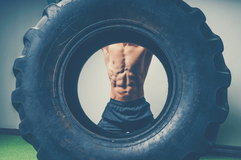 man training abs using a big tire