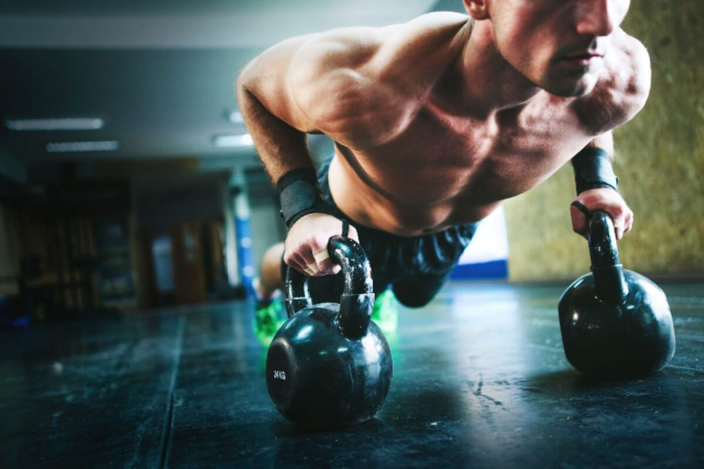 man doing push-ups on top of a kettlebell